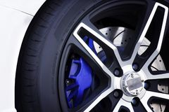 Black magnesium alloy wheels of racing car. Black magnesium alloy wheels of racing car with metal brake discs and blue caliper. Automotive parts concept Stock Image