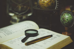 Black Magnifying Glass Beside Gold Ball Point Pen on the Open Book Page Stock Photos