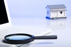 Black magnifying glass on laptop and house Royalty Free Stock Images