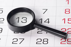 Black magnifying glass over calendar. Black magnifying glass over slightly defocused calendar background Royalty Free Stock Photo