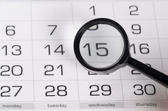 Black magnifying glass over calendar Stock Image