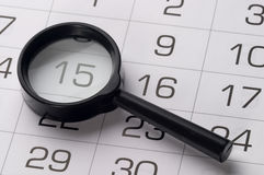 Black magnifying glass over calendar. Black magnifying glass over slightly defocused calendar background Royalty Free Stock Image
