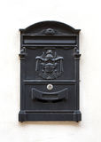 Black mail box. On white wall Stock Images
