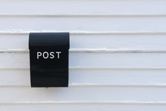 Black mail box on white wooden wall of house Stock Photos
