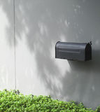 Black mailbox on concrete wall. With the shadow of the tree Royalty Free Stock Images