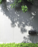Black mailbox on concrete wall. With the shadow of the tree Royalty Free Stock Image