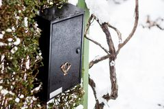 Black mailbox outside a family home. Black mailbox with a golden post office symbol on a winters day stock photography