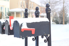 Mailboxes with Snow. Black Mailboxes with white Snow Cover at the top and Red Handle Royalty Free Stock Images