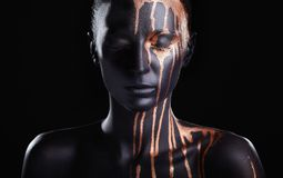 Black makeup. Art fashion makeup. An amazing woman with black makeup and leaking gold paint stock photos