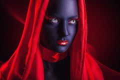 Black makeup. Young woman in a red cape with black makeup on a dark background Stock Photo