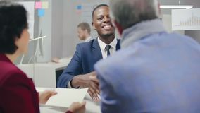 Black male ambitious bank employee smiling. And giving loan agreement to elderly couple and shaking their hands stock footage