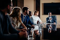 Black male boss talking to business team in conference room. Smiling black male boss talking to business team in conference room Royalty Free Stock Photo