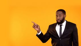 Black male in business suit pointing with finger left, looking to cam, template. Stock photo stock image