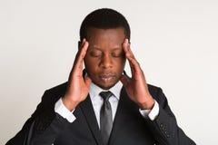 Black male businessman in stylish suit, hand on head, headache. Portrait stock photo