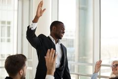 Black male coach hold teambuilding activity with workers raising. Black male mentor hold teambuilding meeting with diverse colleagues, mixed employees involved royalty free stock image