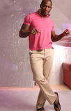 Black male dancing. Black male with tattoo snapping his fingers and dancing he's wearing a pink polo top and khaki pants Royalty Free Stock Photo