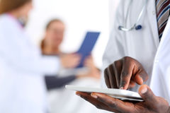 Black male doctor hand point with finger in digital tablet pc. Touch screen with patient lying in bad in background. Professional equipment, therapeutist ward Royalty Free Stock Photos