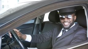 Black male driver sitting in car and smiling into camera, transportation service. Stock photo Stock Photo