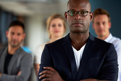 Black male executive with arms crossed facing camera Stock Photos