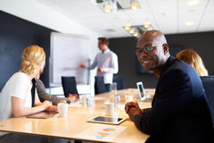 Black male executive smiling at camera during meeting stock photo