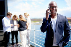 Black male executive smiling while on cellphone. Black male executive smiling holding cellphone to ear and standing with hand in pocket Royalty Free Stock Images