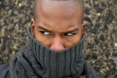 Black male fashion model with gray scarf covering face. Close up portrait of a black male fashion model with gray scarf covering face Royalty Free Stock Image