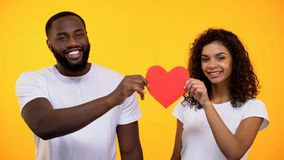 Black male and female holding paper heart smiling camera, relations connection. Stock photo stock images