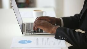 Black male hands typing on laptop keyboard at office desk stock footage