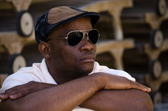 Black male with hat and sunglasses. A black male with hat and sunglasses sat down with arms folded looking into the distance Royalty Free Stock Photos