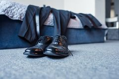 Black male leather shoes on floor in bedroom with business suit placed on bed. In the background Stock Photo