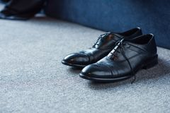 Black male leather shoes placed. On carpet floor Stock Image