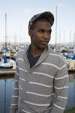 Black male model wearing sweater and newsboy hat at waterfront. Attractive black male model wearing a gray striped sweater and a newsboy hat Royalty Free Stock Images