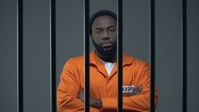 Black male prisoner standing with hands crossed on chest and looking to camera. Stock footage stock footage