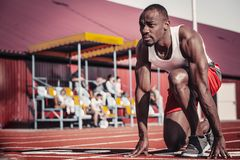 Black male runner with a purposeful look ahead at the start. A black male runner with a purposeful look ahead plays muscles in the sun at the start Royalty Free Stock Image