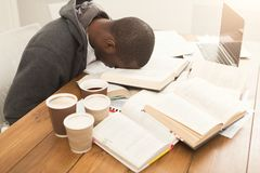 Black male student studying at table full of books. Tired african-american student sleeping on working table. Exhausted male student preparing for exams Stock Photo