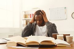 Black male student studying at table full of books. Tired african-american student studying at working table. Exhausted male student preparing for exams Royalty Free Stock Photo