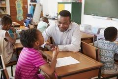 Black male teacher helping elementary school girl in class stock image
