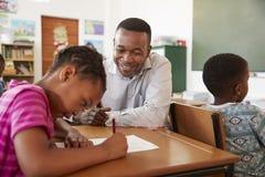 Black male teacher helping elementary school girl in class royalty free stock photos