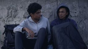 Black male teen supporting homeless friend sitting street, poverty threshold