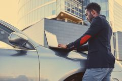 Black male using a laptop on car`s hood. Black male using a laptop on car`s hood over modern building background Stock Photos