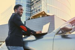 Black male using a laptop on car`s hood. Black male using a laptop on car`s hood over modern building background Stock Image