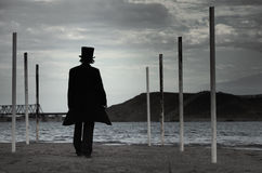 Black man. Rear view on alone man in the black coat and top-hat going to the sea. Natural darkness. Artistic colors added Stock Photos