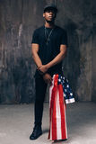 Black man with american flag as accessory. On dark background. Casual guy ready to celebrate. Patriot, national event celebration, independence day, pride Royalty Free Stock Image