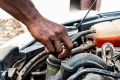 Black man as Auto mechanic working in garage near car engine. Repair service and transport concept. Hands of African American car royalty free stock photo