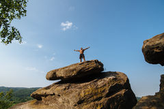 Black man athlete stands on a rock against the blue cloudy sky Royalty Free Stock Photography