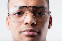 Black man with big ugly glasses. Young afro-american man close up portrait with out of fashion glasses in nineties style Royalty Free Stock Images
