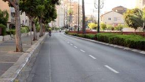 Black man biking in deserted city stock video