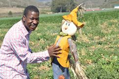 Black man in a California farm playing with a scarecrow Stock Photo