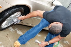 Black man cleaning car 2. Man washing the wheels of his car holding a hose and sprayer royalty free stock images