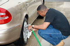 Black man cleaning car 3. A view of an African American man bending down to wash a tire and wheel of a car Royalty Free Stock Image